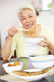 Senior Chinese Woman Sitting At Home Eating Meal — Stock Photo