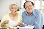Senior Chinese Couple Sitting At Home Eating Meal — Стоковое фото