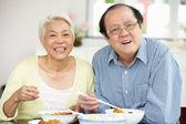 Vysocí čínští pár sedět doma a jídlo — Stock fotografie