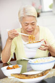 Donna cinese anziano seduto a casa a mangiare il pasto — Foto Stock