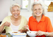 Due donne cinesi anziani seduti a casa a mangiare il pasto — Foto Stock