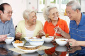 Gruppo di amici cinesi senior mangiare il pasto a casa — Foto Stock