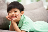 Young Chinese Boy Relaxing On Sofa At Home — Stock Photo
