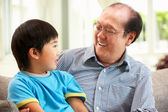 Chinese Grandfather And Grandson Relaxing On Sofa At Home — Stock Photo