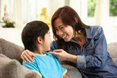 中国母亲和儿子在家里的沙发上坐在一起 — 图库照片