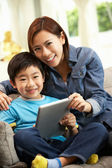 Kinesiska mor och son använder tablet pc samtidigt sitter på s — Stockfoto