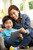 čínská matka a syn pomocí tabletového počítače, zatímco sedí na s — Stock fotografie