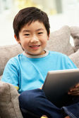 Young Chinese Boy Using Tablet Computer Whilst Sitting On Sofa A — Stock Photo