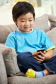 Young Chinese Boy Using Mobile Phone On Sofa At Home — Stock Photo