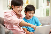 Padre cinese e figlio usando il portatile mentre vi rilassate sul divano a h — Foto Stock