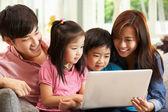 Usando o laptop, enquanto relaxa no sofá em casa de família chinesa — Foto Stock