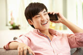 Young Chinese Man Using Mobile Phone On Sofa At Home — Stock Photo