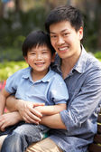 Homem chinês com filho relaxando no banco do parque — Foto Stock
