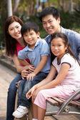 китайская семья, ходьбе, сидя на скамейке в парке вместе — Стоковое фото