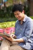 Young Chinese Man Using Digital Tablet Whilst Relaxing On Park — Stock Photo