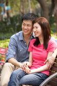 Mladý čínský pár odpočinkem na lavičce v parku společně — Stock fotografie