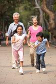 Chinese Grandparents Walking Through Park With Running Grandchil — Stock Photo