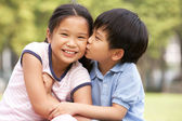 Portrait Of Chinese Boy And Girl Sitting In Park Together — Stock Photo