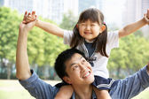 Chinese Father Giving Daughter Ride On Shoulders In Park — Stock Photo