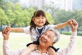 Abuelo chino llevar nieta en hombros en pa — Foto de Stock