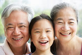 Head And Shoulders Portrait Of Chinese Grandparents With Grandda — Stock Photo