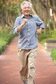 Senior chinese man joggen in het park — Stockfoto