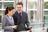 Businessman And Businesswoman Discussing Document Outside Office — Stock Photo