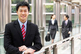 Portrait Of Chinese Businessman Outside Office With Colleagues I — Stock Photo