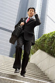 Chinese Businessman Rushing Down Steps On Mobile Phone — Stock Photo