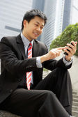 Chinese Businessman Dialling On Mobile Phone Outside Office — Stock Photo