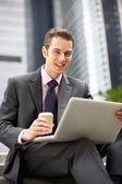 Uomo d'affari, lavorando sul portatile fuori ufficio con caffè da asporto — Foto Stock