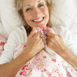 Senior Woman Relaxing In Bed — Stock Photo