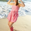 Teenage Girl Wearing Wellington Boots Splashing In Sea On Beach - Stock Photo