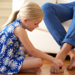 Daughter Painting Father's Toenails At Home - Стоковая фотография