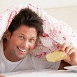 Stock Photo: MSnuggled Under Duvet Eating Breakfast