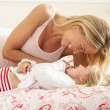 Mother And Daughter Relaxing Together In Bed - Stock Photo