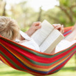 Stock Photo: Senior Woman Relaxing In Hammock With Book