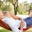 Stock Photo: Senior Couple Relaxing In Hammock