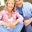 Senior Couple Sitting Outside House — Stock Photo #24638345