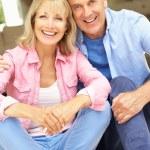 Senior Couple Sitting Outside House — Stock Photo #24638345