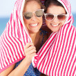 Stock Photo: Two Women Sheltering From Sun On Beach Holiday