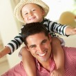 Stock Photo: Father Giving Son Ride On Shoulders Indoors