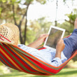 Senior Man Relaxing In Hammock With  E-Book — Stockfoto