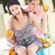 Stock Photo: MPushing WomIn Wheelbarrow Filled With Oranges