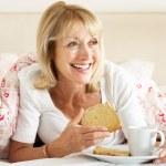 Senior Woman Snuggled Under Duvet Eating Breakfast — Stock Photo #24638493