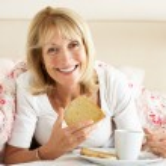 Senior Woman Snuggled Under Duvet Eating Breakfast — Stock Photo #24638535