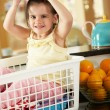 Girl Sitting In Laundry Basket On Kitchen Counter With Lemon - Foto Stock