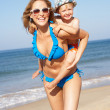 Mother And Son Running Along Beach — Stock Photo #24638601