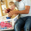 Father And Son Sorting Laundry Sitting On Kitchen Counter - Foto Stock