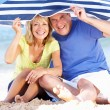 Stock Photo: Senior Couple Sheltering From Sun Under Beach Umbrella